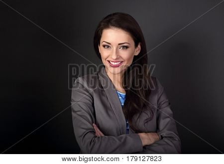 Beautiful Toothy Smiling Business Woman In Grey Suit Looking Happy With Folded Arms On Dark Grey Bac