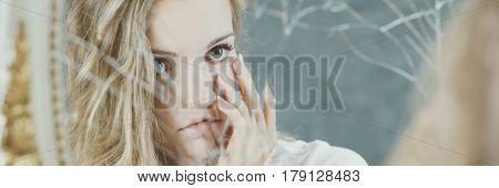 Young blonde girl looking at broken mirror