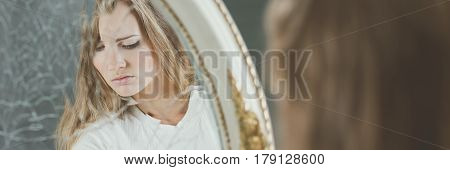 Mirror with reflection of depressed girl, panoramic
