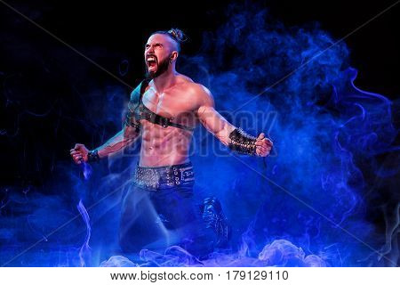 Handsome young sexy man with beautiful muscular chest in interesting costume on the scene. The Stripper man. Show time