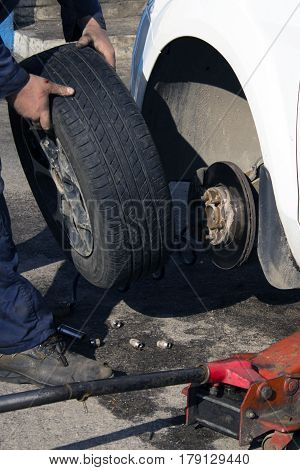 Hands Of Mechanic Changing Car Wheel In Auto Repair Service