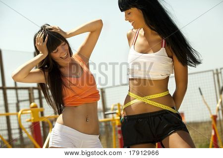 Young woman measuring waist with tape measure and her girlfriend envies her