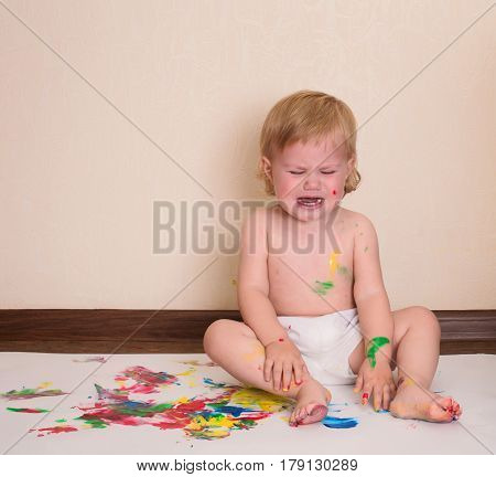 Baby crying. Dirty child drawing with her fingers. Toddler painting. Cry baby with finger paints at home.