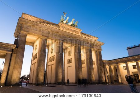 Berlin Germany - February 24 2017: Illuminated famous neoclassical triumphal arch of Brandenburg Gate one of the best-known landmarks of Germany in Berlin just after sunset .