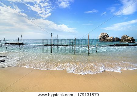 Wooden poles for fishing on a beach of indian ocean in Sri Lanka