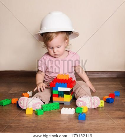Cute baby in protective helmet playing with plastic constructor blocks building a house. Little builder.