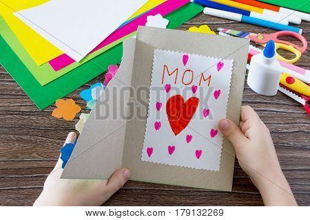 Ребенок держит открытку платье с цветами в День матери. Детский художественный проект, ремесло для д