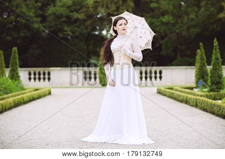 Woman in white Victorian dress with umbrella in park