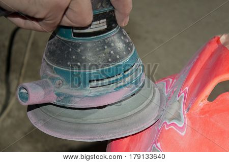 Work polishes the car body component preparation before painting.