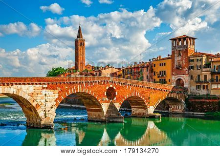 Panoramic view to Bridge Ponte Pietra in Verona on Adige river, Veneto region, Italy. Sunny summer day panorama and blue dramatic sky with clouds. Ancient european italian terracotta color houses.