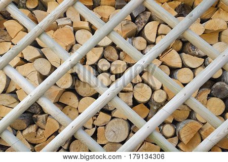 background of a pile of firewood neatly stacked behind a wooden fence