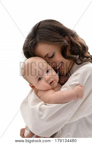 Young pretty mother keeping lovely baby boy in her arms smiling affectionately at him studio shot