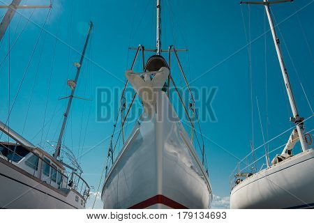 nose of white beautiful moored sailboat in the sea port