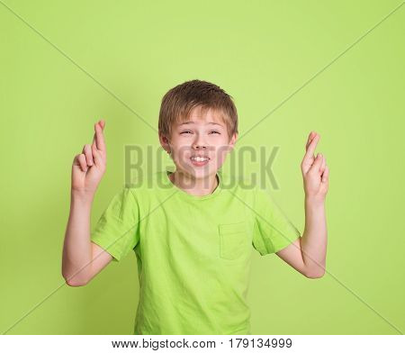 Funny boy crossing his fingers and wishing for good luck