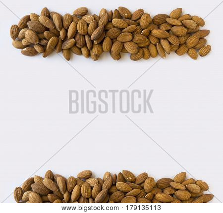 Almonds at border of image with copy space for text. Kernels almonds on a grey background. Top view. Vegetarian or healthy eating. Background of almond.