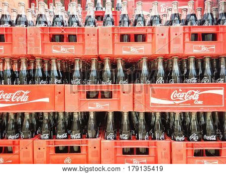 BANGKOK, THAILAND - MARCH 30: Empty recycle bottles of Cola in red plastic box on March 30, 2017 in Bangkok, Thailand.Cola drinks are produced and manufactured by The Cola Company