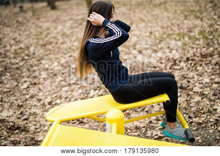 Sporty Woman Doing Abdominal Exercises, Reverse Crunches In Outdoor Park.