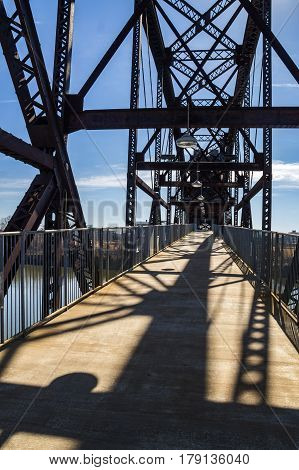 Steel structure of pedestrian bridge across river with shadows.  Clinton Presidential Park in Little Rock, Arkansas