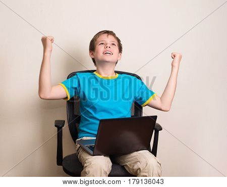 Happy teen boy with laptop in winning pose. Success kid in office chair with portable pc happy ecstatic celebrating being a winner.