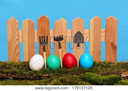 Painted Easter Eggs At Wooden Fence On Green Moss