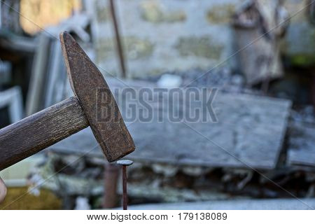 Old hammer hammering a nail into a wooden board