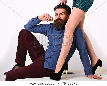bearded man long beard brutal caucasian hipster with moustache on serious face with female sexy legs in fashionable shoes and green sequins skirt isolated on white background getting haircut