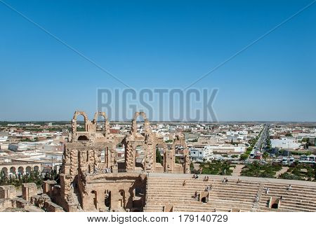 Wall of the Coliseum in Tunisia against the backdrop of the city and the clear cloudless blue sky