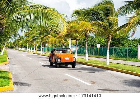 Orange Car With Man Driver On Road, Cozumel, Mexico