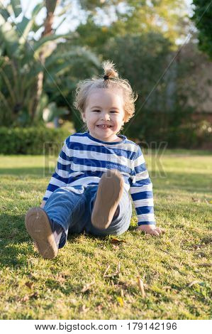 Small Baby Boy With Happy Face On Green Grass Barefoot