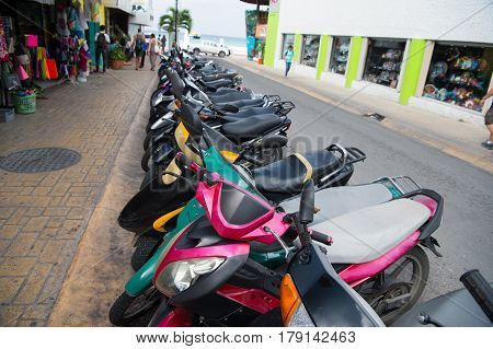 colorful scooters or motorcycles for sale or hire standing in row with wheels and lights on street road outdoor in Cozumel Mexico hiring transportation traveling