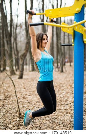 Fit Woman Training Pull Ups In City Park Outdoors. Health Concept.
