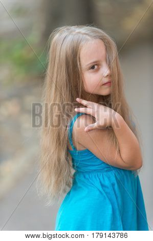 Small Baby Girl With Long Hair In Blue Dress Outdoor