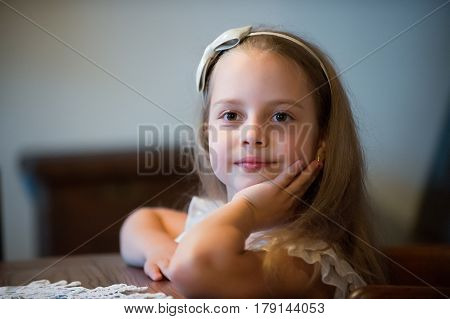 Small Baby Girl With Smiling Face Sitting At Table
