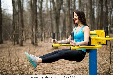 Portrait Of Strong Young Woman Hanging On Wall Bars With Her Legs Up. Fitness Woman Performing Hangi