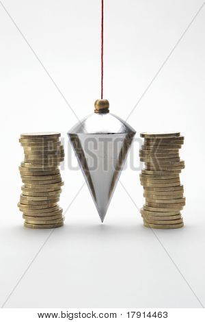 Plumb bob with coin stacks on white background