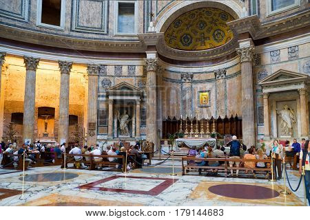ROME, ITALY - OCTOBER 2, 2012: Tourists visit the main altar of the Pantheon. Roman Pantheon is a famous monument of ancient Roman culture the temple of all the gods built in the 2nd century.