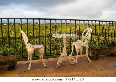 White vintage wrought iron gardening furniture, set of empty round table and two elegant chairs on the balcony, green vineyards in the background