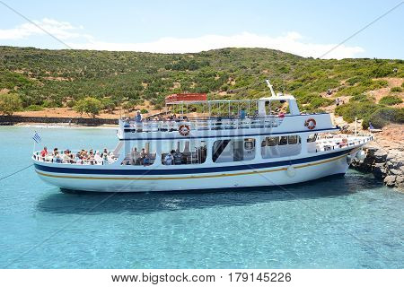 SPINALONGA GREECE - MAY 14: The motor yacht with tourists is near Spinalonga island on May 14 2014 in Spinalonga Greece. Up to 16 mln tourists is expected to visit Greece in year 2014.