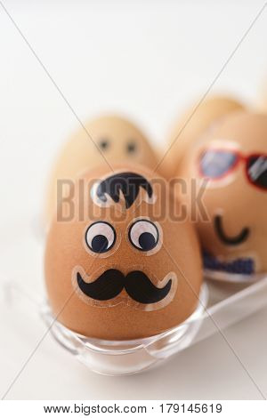 closeup of some easter eggs decorated with funny faces in a plastic egg tray