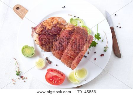 Rolled stuffed roast pork with spices on a white plate.