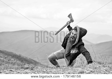 bearded man long beard brutal caucasian hipster with moustache holds axe with angry face on mountain top with cloudy sky unshaven guy with stylish hair getting beards haircut black and white