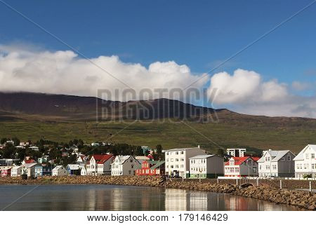 beautiful colorful coastal houses near green mountain and water on blue cloudy sky background sunny outdoor in nothern Iceland Akureyri. traveling and vacation wanderlust