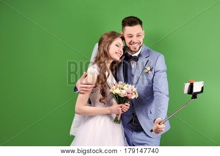 Happy wedding couple taking selfie on color background