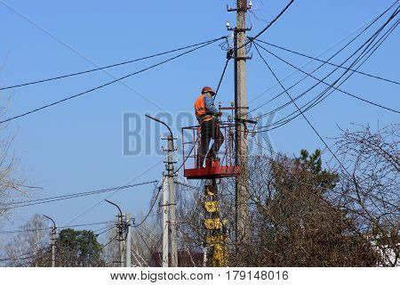 The electrician is changing the wires on the pole