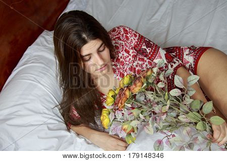 Beautiful young caucasian girl with closed eyes lying on the bed holding a bouquet of dried flowers. The bed has white sheets and she is wearing a dress with a print of red flowers.