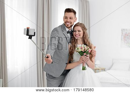 Happy wedding couple taking selfie at home