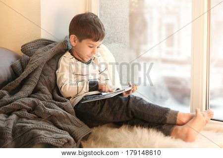 Cute little boy reading book while sitting on window sill at home