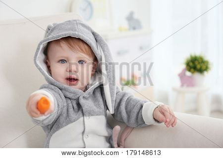 Cute little baby in bunny costume with carrot in hand sitting on armchair at home