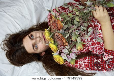 Beautiful young caucasian girl with blue eyes lying on the bed holding a bouquet of dried flowers. The bed has white sheets and she is wearing a dress with a print of red flowers.