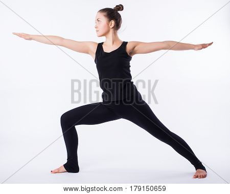 Young yoga woman warrior pose. This is part of a series of various yoga poses by this model, isolated on white.